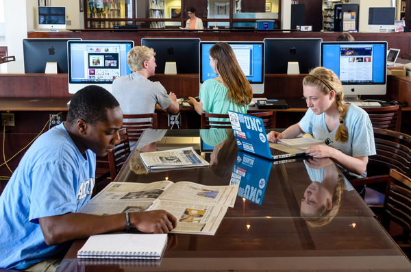 Students studying at tables and screens in the Park Journalism Library