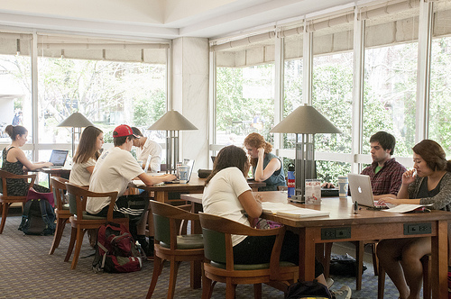 Students studying at tables in front of windows in the Undergraduate Library Reserves Reading Room