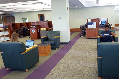 large tables and individual carrels in an open space in the Undegraduate Library reference room