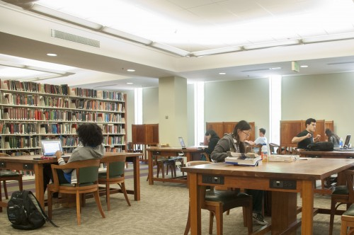 Students studying at tables in the upper stacks of the Undergraduate Library.