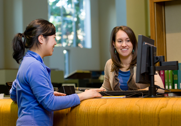 Librarian helping student with research at service desk