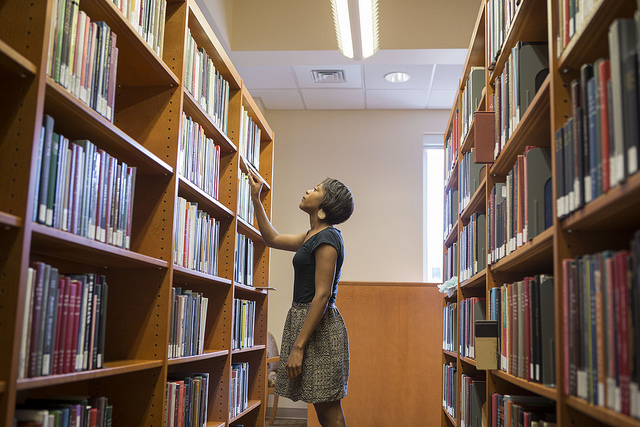 a student stands in the stacks, ready to pull a book off the shelf.