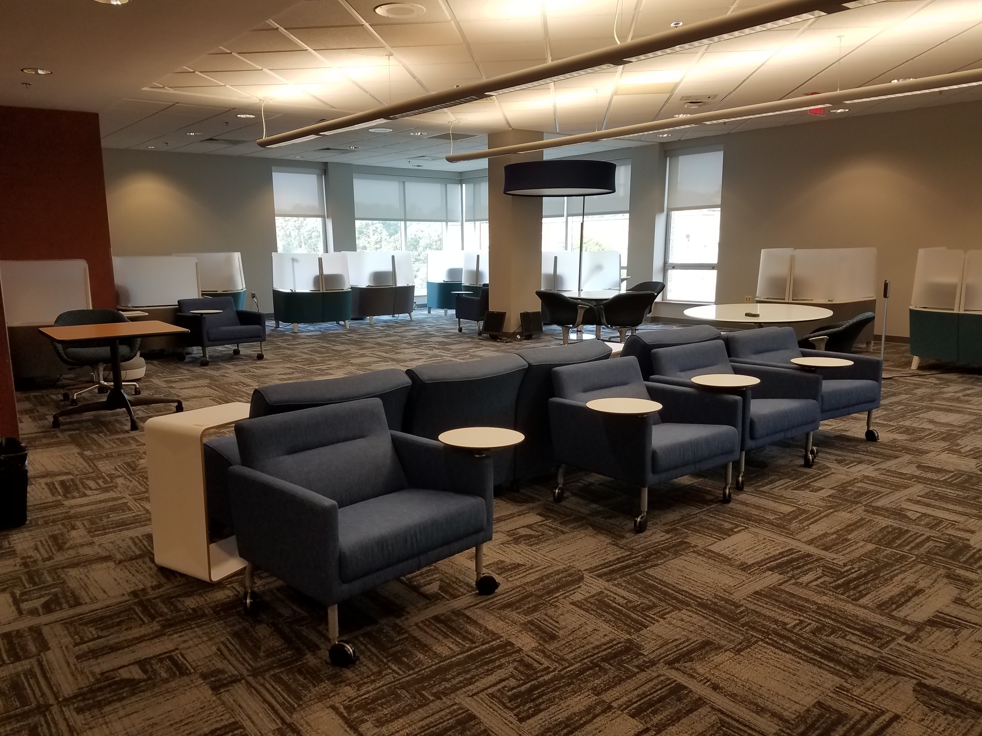 movable chairs with arm desks, next to individual study pods.