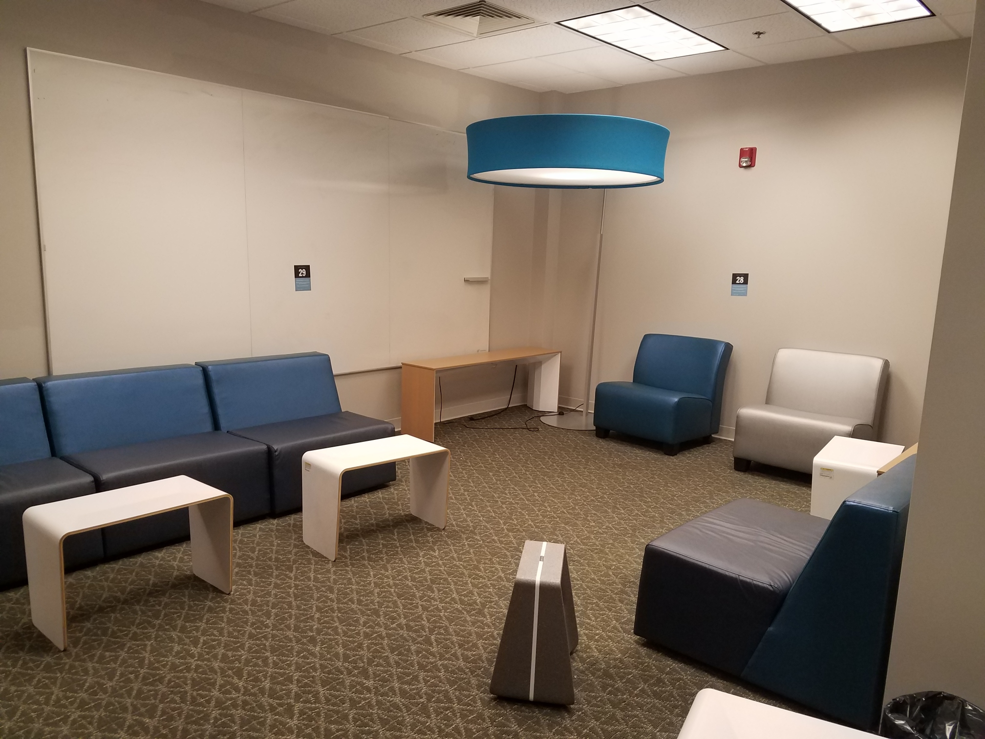 couches and small tables, with a large whiteboard.