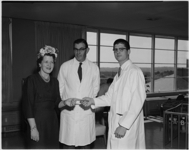 Department of Pediatrics Dr. Berryhill and Dr. Denny receiving donation from Mrs. Kitchen, 1961.  Photographic Laboratory, #P0031, North Carolina  Collection Photographic Archives.