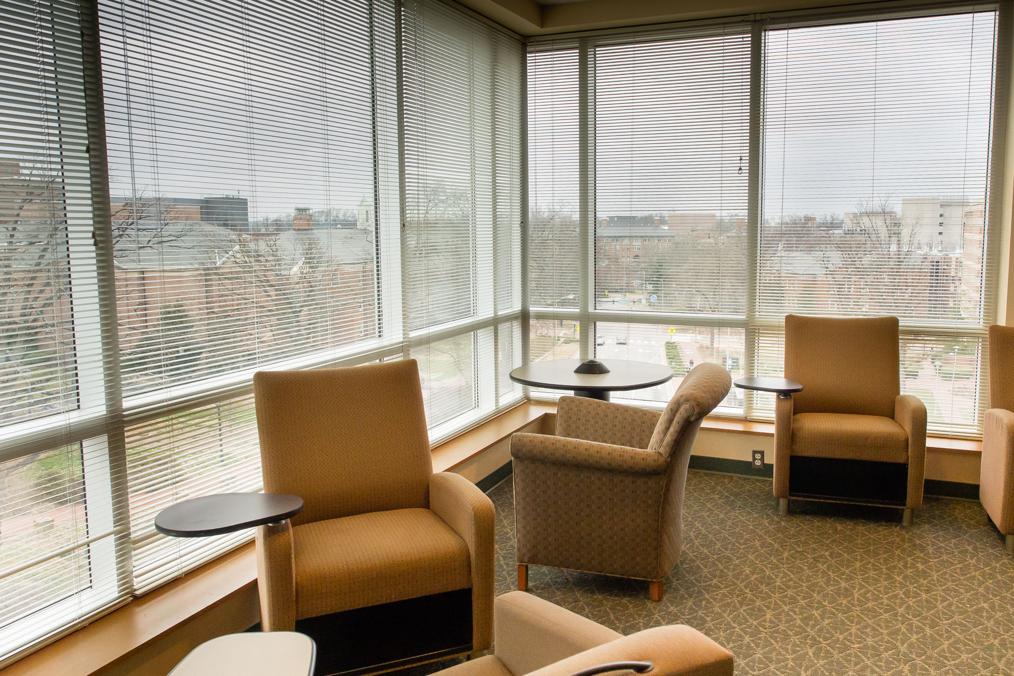 Moveable, comfy chairs with armrests in a well-lit windowed corner of Health Sciences Library's fourth floor