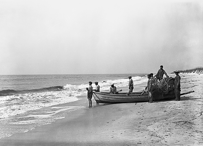 a boat with fishermen on a beach