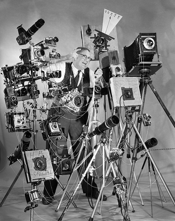 """Photographer Joe Clark (a.k.a. """"Hill Billy Snap Shooter"""") posing with a large display of multiple cameras. Photograph by Hugh Morton."""