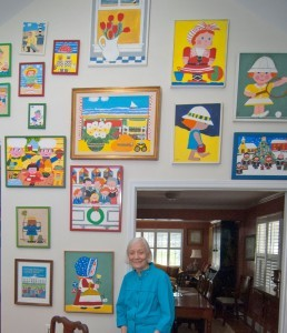 Image of Betty Debnam Hunt posing next to a wall with artwork.