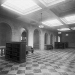A room with arched doorways and a checkered floor with a few wooden shelves of books and two benches.