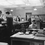 Young white men with short hair at work behind a library circulation desk. Several other young white men with short hair approach the desk for assistance.