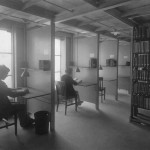 Study carrels in the library stacks. Each carrel has a pendant light, a shelf, a window, and a desk and chair. Two carrels are occupied - one by a young man and one by a young woman.