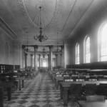 A large reading room with a checkered floor, many long tables with chairs, tall arched windows, chandeliers, and columns.