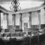 The rotunda of the reading room, featuring columns, a large circular desk, and a chandelier.