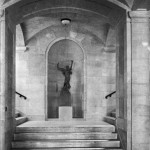 A sculpture of a winded woman in a dress holding a branch and a bowl in her raised hands. The sculpture is in a niche on the landing of a staircase. Stairs ascend on either side of the niche, and descend in front of the landing.