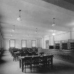 An empty reading room with tables, chairs, a row of shelving, windows, and pendant lights.