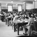 A crowded reading room of young white men and women studying at long tables. There are about six students at each table.