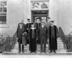 Eight white men with short hair, middle aged and older, stand in front of a building entrance. Four wear dark academic robes and mortarboards. Four are wearing dark suits.