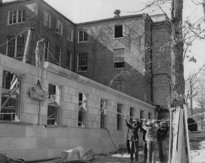 Five men wearing hats use a pulley to lift concrete molding during construction of the 1952 addition to Wilson Library.