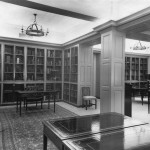 A room lined with bookshelves, with a small chandelier and several wood tables.