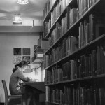 A young white woman with a ponytail studies at a carrel in the Wilson Library stacks. There are posters behind her on the wall. A shelf of books is in the foreground.