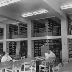 Three young white men with short hair study at tables in a room in the Wilson Library stacks. Two floors of stacks are visible in the background.