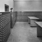 A room lined with card catalogs. There are two empty tables in the center.