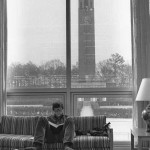 A young white man with short hair and glasses reads a book on a couch in a Wilson Library lounge. Large windows behind him show the Bell Tower. He has his feet up on a coffee table and his shoes are on the floor.