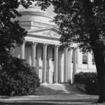 A black and white view of the front of Wilson Library and its dome, framed by trees.