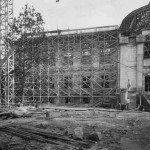 A black and white photo of Wilson Library under construction, with scaffolding up its side.