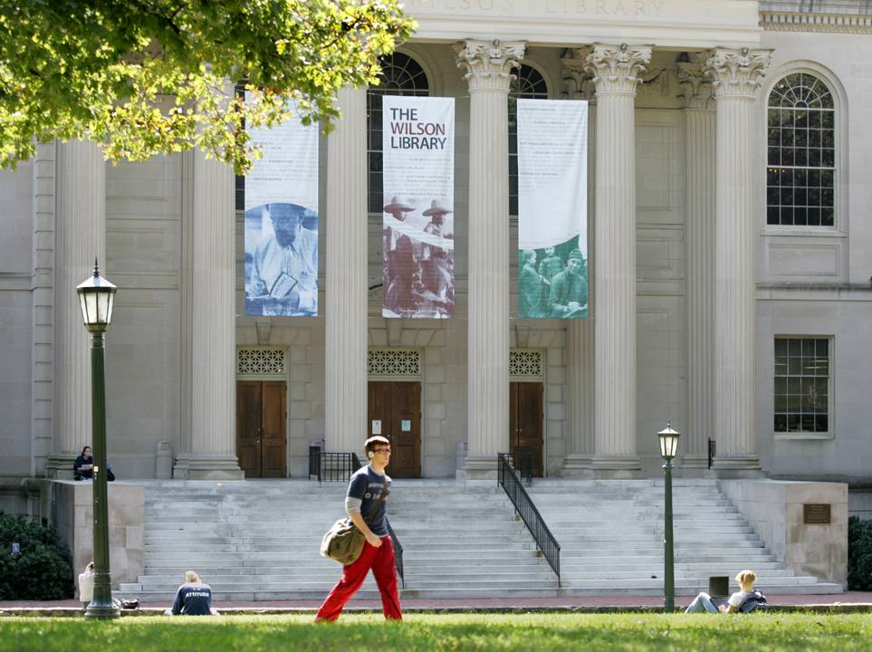 A color photo of a young man wearing red pants and carrying a messenger bag walking in front of Wilson Library. Two students are seated in the grass behind him.
