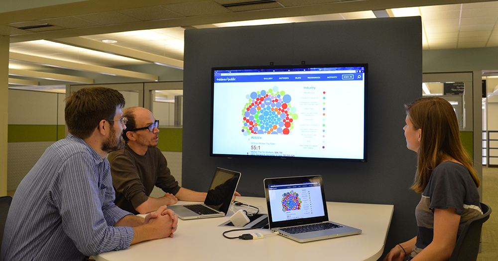 Three people using a large, mounted display at the Research Hub Collaboration Table