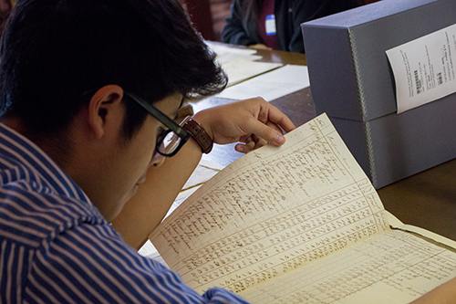 Student Adonis Tello-Chavez looking at records in Wilson Library