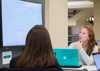 students working together at a collaboration table in the Davis Library Research Hub
