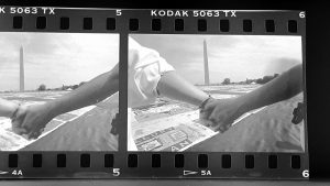 Hands clasped together in front of AIDS Memorial Quilt display on National Mall