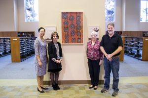A new painting in UNC's Davis Library honors the memory of librarian Will Owen, who was an expert in Australian Aboriginal art. Left to right: University Librarian Elaine Westbrooks, Chancellor Carol Folt, former University Librarian Sarah Michalak, and Associate University Librarian Tim Shearer.