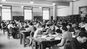 Historic black-and-white photo of people studying in Wilson Library reading room.