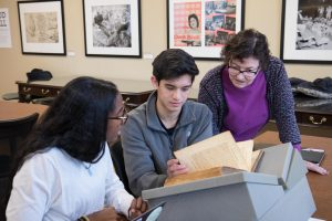 Students and teacher looking at rare books in Wilson Library