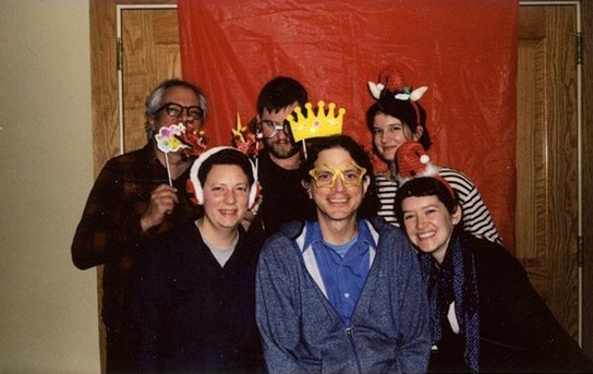Staff pose for holiday party picture with goofy hats