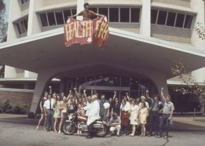 a group of african-american students standing in front of a building, with a banner reading Health Fair held above.