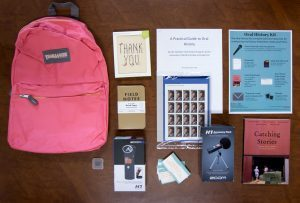 A backpack with oral history interview supplies laid out next to it.
