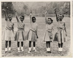 five young African-American girls stand in a field with their right fists raised.
