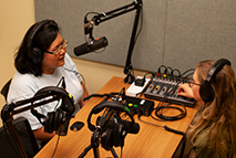 two students in a recording studio with microphone, headsets, and a mixing board
