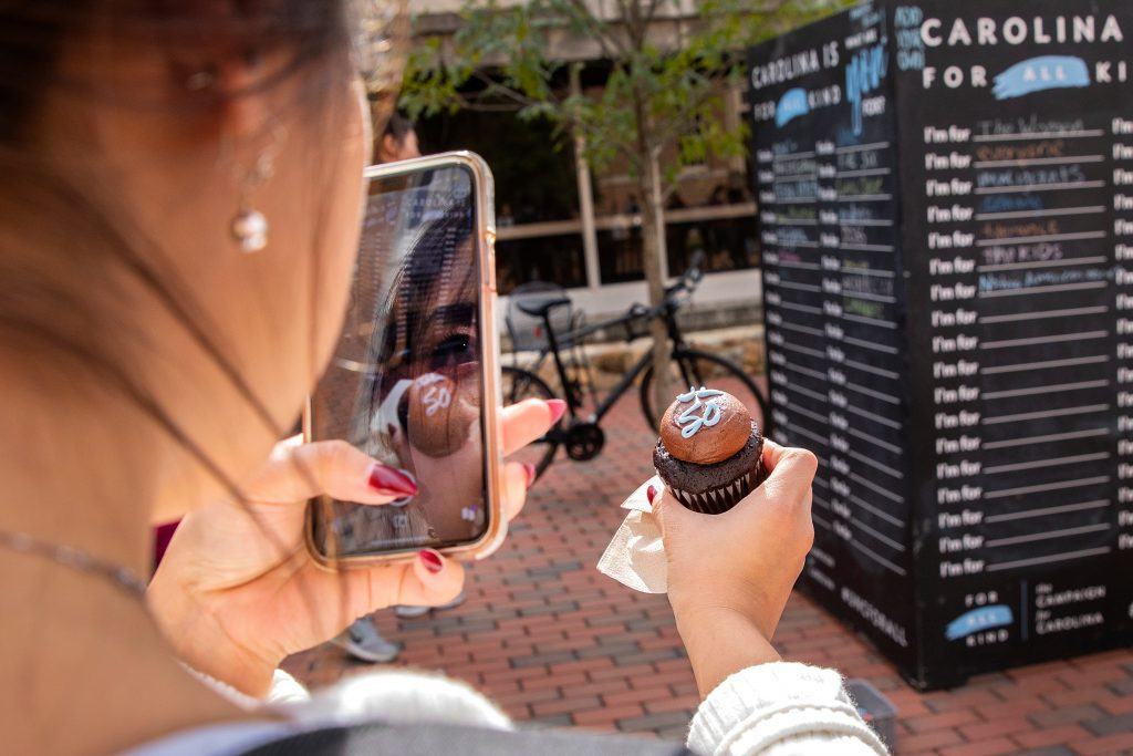 Student takes an iPhone photo of their cupcake during UL 50th celebration