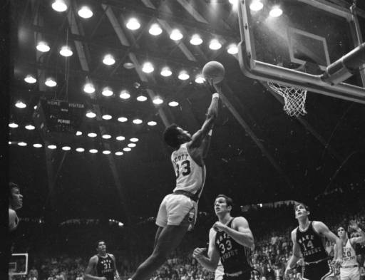In this image from a 1968 game between UNC Chapel Hill and Wake Forest, Tar Heel basketball player Charlie Scott jumps to make a shot over two Wake Forest players in a crowded gym. The image is from the Hugh Morton Photographic Collection, North Carolina Collection Photographic Archives, Wilson Special Collections Library.