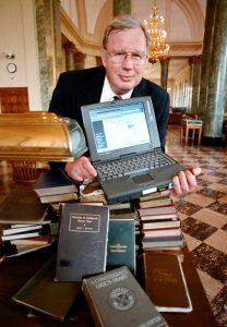 Joe Hewitt holding laptop computer with books