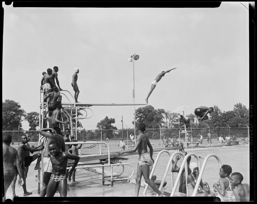 a black community pool; children diving off the diving board.