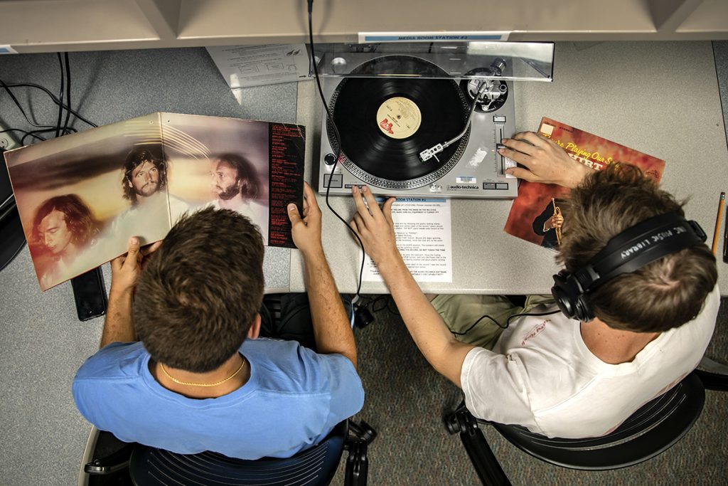 two students listening to a vinyl record at a turntable booth in the Music Library