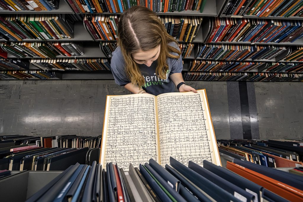 student holding a book of sheet music in the Music Library stacks