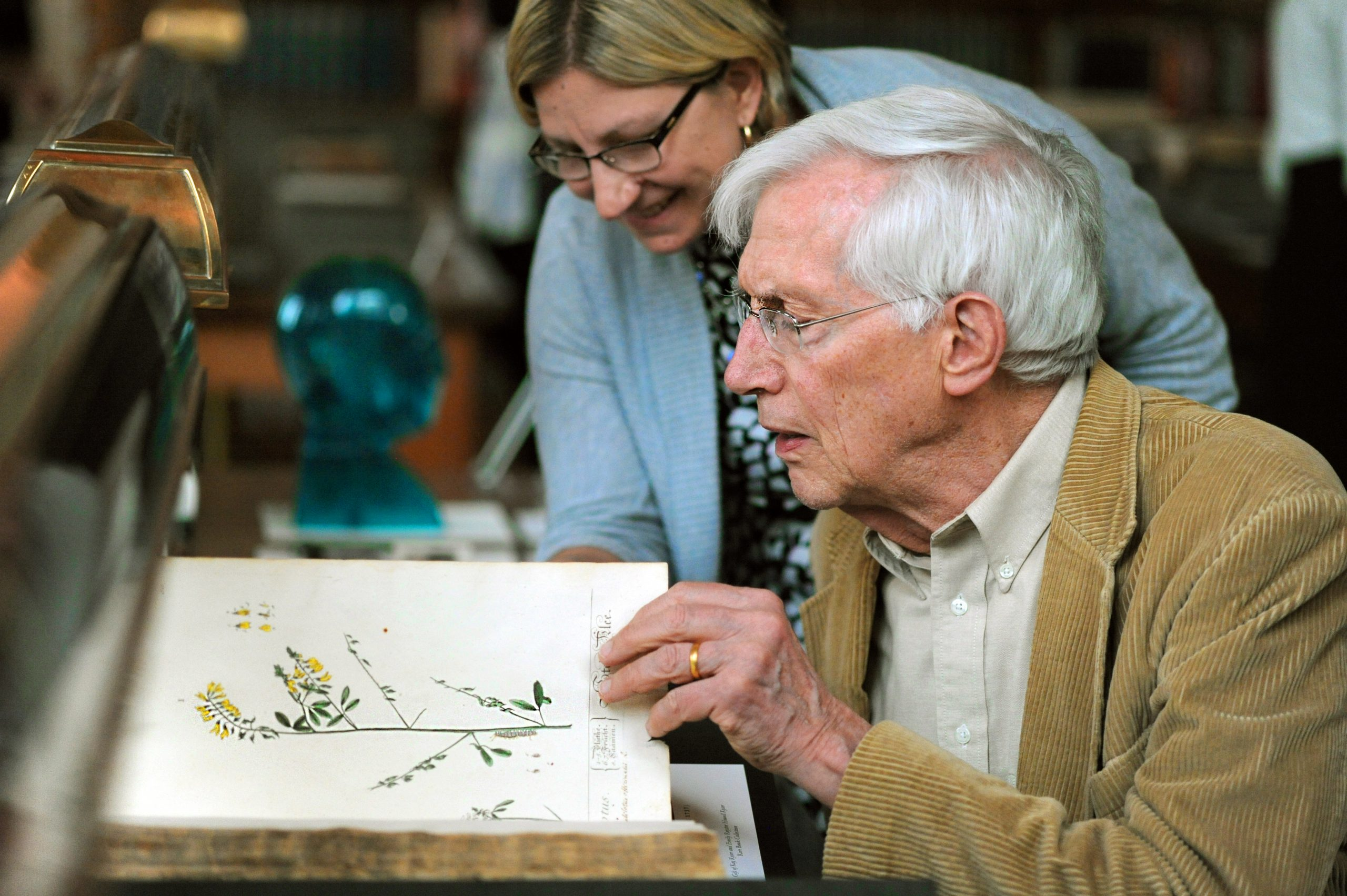 Librarian Dawne Lucas and professor emeritus Michael McVaugh looking at a book of flowers